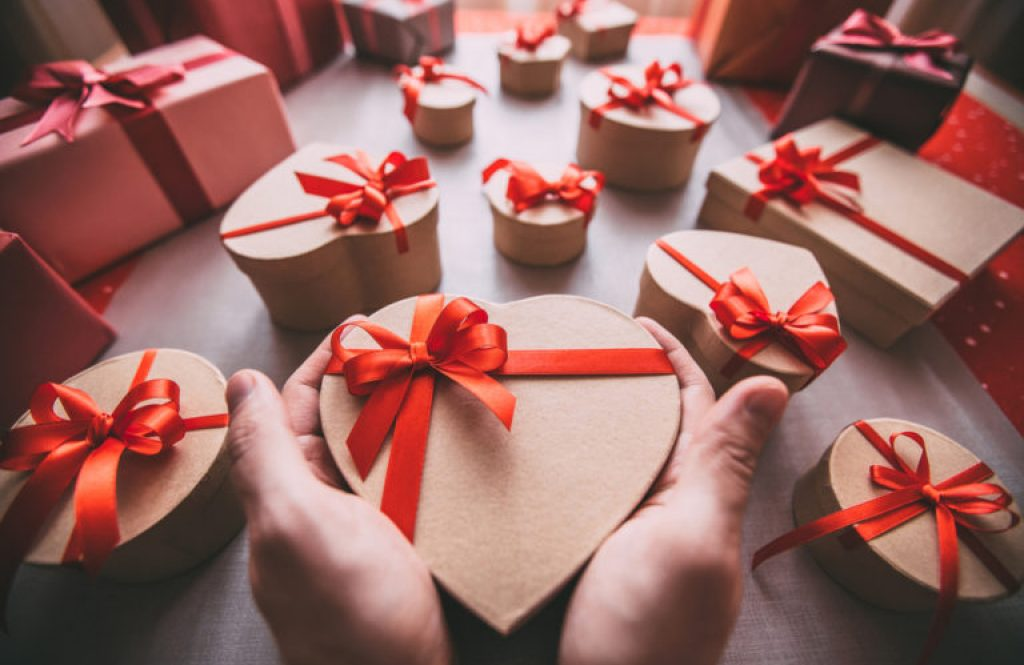 Men's hands hold a gift heart shape. Give a gift.